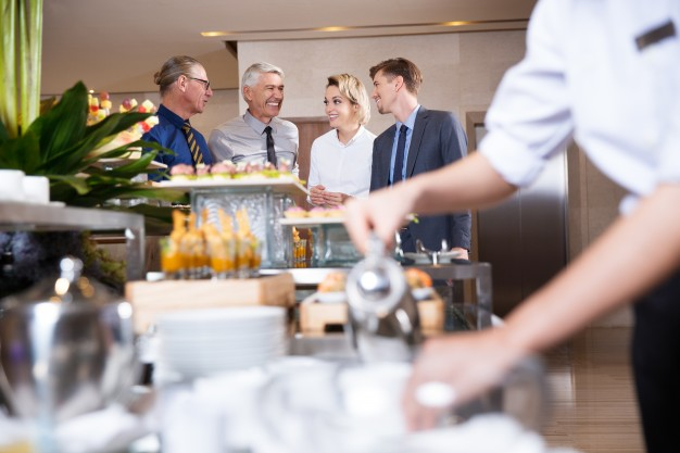 four-smiling-business-people-buffet-table_1262-1832